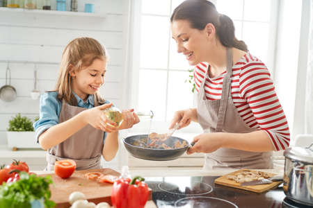 Photo pour Healthy food at home. Happy family in the kitchen. Mother and child daughter are preparing proper meal. - image libre de droit