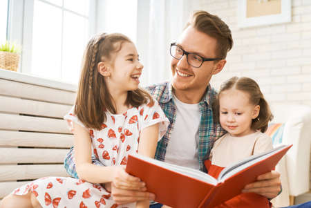 Happy loving family. Young father reading a book to his daughters.