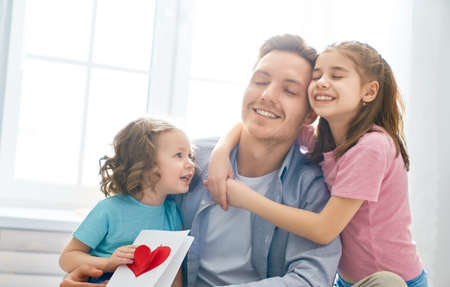 Photo pour Happy father's day! Children daughters congratulating dad and giving him postcard. Daddy and girls smiling and hugging. Family holiday and togetherness. - image libre de droit
