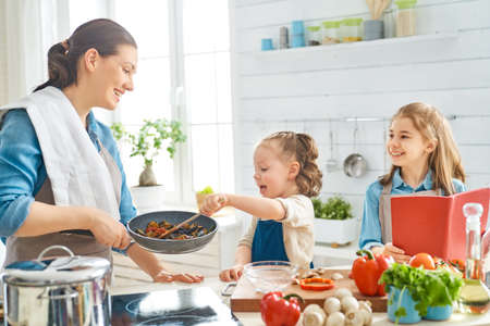 Photo pour Healthy food at home. Happy family in the kitchen. Mother and children daughters are preparing vegetables. - image libre de droit
