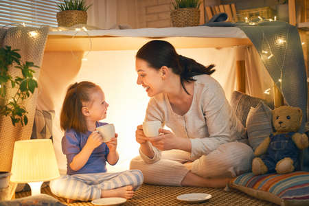 Foto de Happy loving family. Mother and her daughter girl play tea-party and drink tea from cups in children room. Funny mom and lovely child having fun indoors. - Imagen libre de derechos