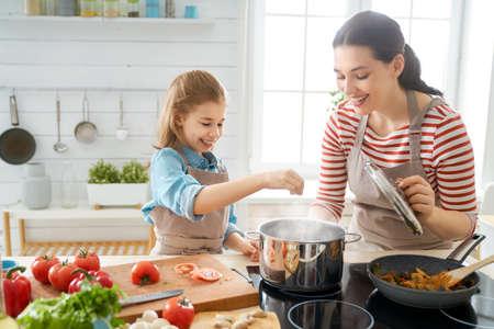Foto de Healthy food at home. Happy family in the kitchen. Mother and child daughter are preparing proper meal. - Imagen libre de derechos