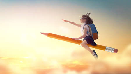 Photo pour Back to school! Happy cute industrious child flying on the pencil on background of sunset sky. Concept of education and reading. The development of the imagination. - image libre de droit