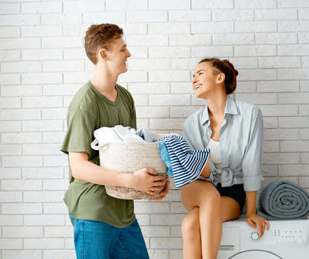 Photo pour Beautiful young loving couple is smiling while doing laundry at home. - image libre de droit