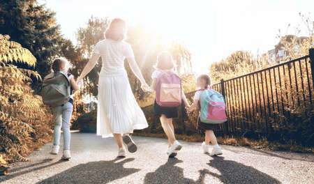 Photo pour Woman and girls with backpacks behind backs. Beginning of lessons. First day of fall. - image libre de droit