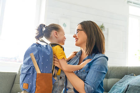 Photo pour Parent and pupil of preschool. Woman and girl with backpack behind back. Beginning of lessons. First day of fall. - image libre de droit