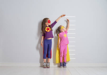 Foto de Two little children are playing superhero. Kids are measuring the growth on the background of wall. Girl power concept. - Imagen libre de derechos