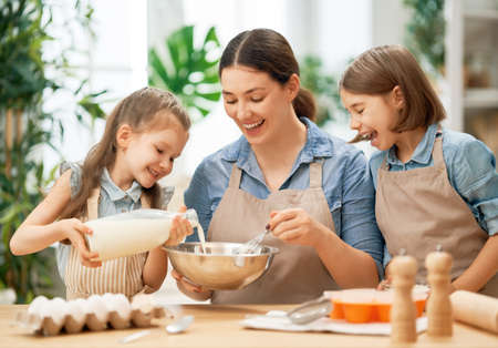Photo pour Happy loving family are preparing bakery together. Mother and children daughters girls are cooking cookies and having fun in the kitchen. Homemade food and little helpers. - image libre de droit