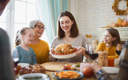 Photo pour Happy Thanksgiving Day! Autumn feast. Family sitting at the table and celebrating holiday. Grandparents, mother, father and children. Traditional dinner. - image libre de droit