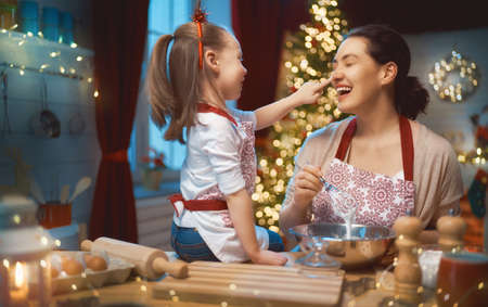 Photo pour Merry Christmas and Happy Holidays. Family preparation holiday food. Mother and daughter cooking cookies. - image libre de droit