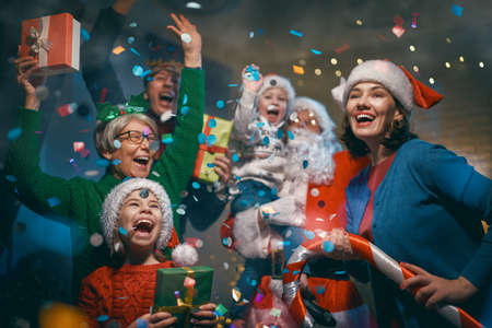 Photo pour Merry Christmas and Happy Holidays! Grandma, grandpa, mum, dad and children having fun near tree indoors. Family party. - image libre de droit
