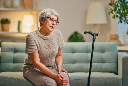 Photo pour Senior woman with cane. Feeling unwell and pain in the knee. - image libre de droit