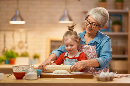 Photo pour Happy loving family are preparing bakery together. Granny and child are cooking cookies and having fun in the kitchen. Homemade food and little helper. - image libre de droit