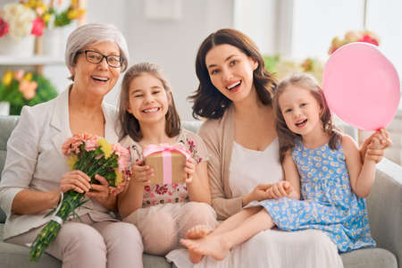 Photo pour Happy women's day! Children daughters are congratulating mom and granny giving them flowers and gift. Grandma, mum and girls smiling and hugging. Family holiday and togetherness. - image libre de droit