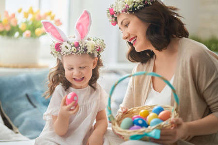 Photo pour Happy holiday! Mother and her daughter with painting eggs. Family celebrating Easter. Cute little child girl is wearing bunny ears. - image libre de droit