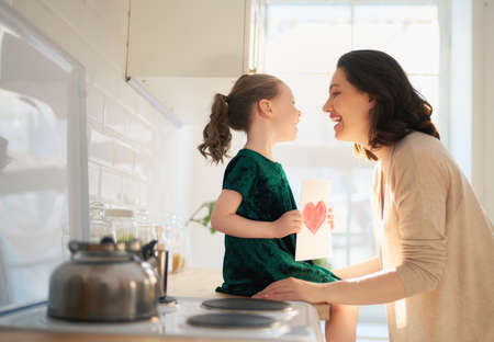 Photo pour Happy mother's day! Child daughter is congratulating mom and giving her postcard. Mum and girl smiling and hugging. Family holiday and togetherness. - image libre de droit