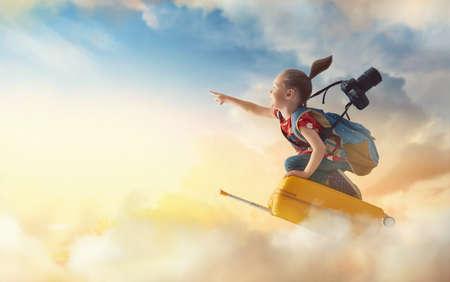 Photo pour Dreams of travel! Child flying on a suitcase against the backdrop of sunset.                                 - image libre de droit