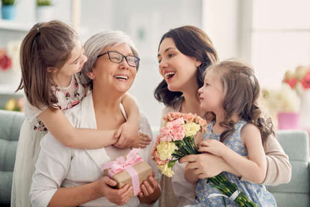 Photo pour Children daughters are congratulating mom and granny giving them flowers and gift. Grandma, mum and girls smiling and hugging. Family holiday and togetherness. - image libre de droit