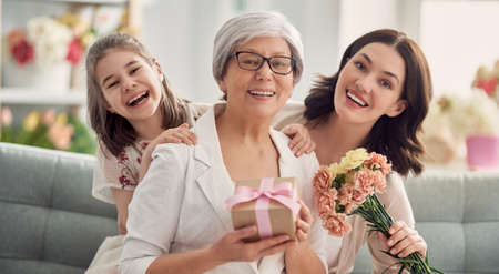 Photo pour Child daughter is congratulating mom and granny giving them flowers and gift. Grandma, mum and girl smiling and hugging. Family holiday and togetherness. - image libre de droit