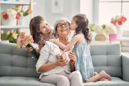 Photo pour Happy mother's day! Children daughters are congratulating granny giving her flowers and gift. Grandma and girls smiling and hugging. Family holiday and togetherness. - image libre de droit