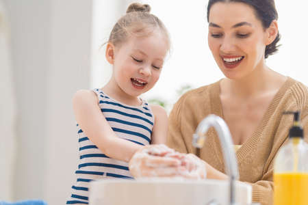 Photo pour A cute little girl and her mother are washing their hands. Protection against infections and viruses. - image libre de droit