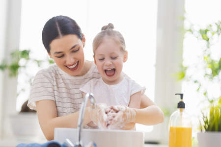 Foto für A cute little girl and her mother are washing their hands. Protection against infections and viruses. - Lizenzfreies Bild