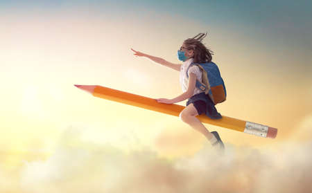Photo pour Back to school after quarantine! Happy cute industrious child with face mask flying on the pencil on background of sunset sky. Concept of education after pandemic. The development of the imagination. - image libre de droit