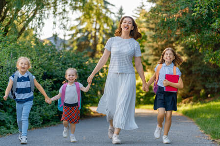 Photo pour Parent and pupils of primary school go hand in hand. Woman and girls with backpacks behind backs. Beginning of lessons. First day of fall. - image libre de droit
