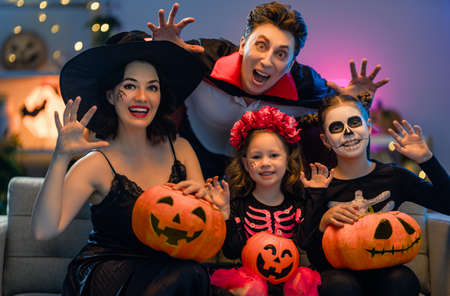 Photo pour Mother, father and their kids having fun at home. Happy family celebrating Halloween. People wearing carnival costumes and makeup. - image libre de droit