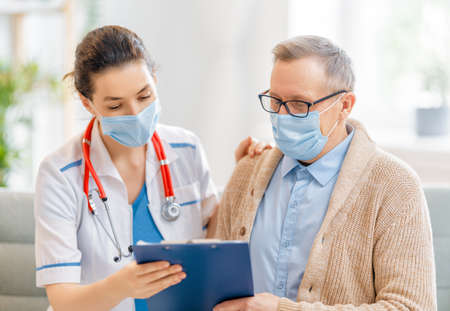 Photo pour Doctor and senior man wearing facemasks during coronavirus and flu outbreak. Virus and illness protection, home quarantine. COVID-2019 - image libre de droit