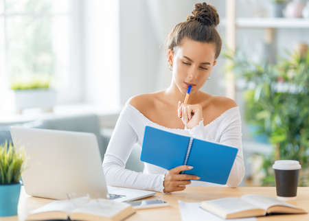 Photo pour Focused young businesswoman studying online, watching webinar, podcast on laptop, making notes, sitting at work desk. E-learning concept. - image libre de droit