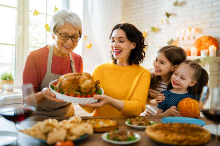 Photo pour Happy Thanksgiving Day! Autumn feast. Family sitting at the table and celebrating holiday. Traditional dinner. Grandmother, mother and daughters. - image libre de droit