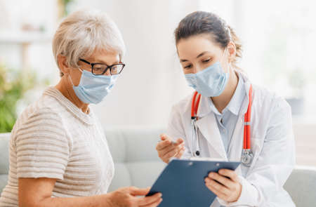 Foto de Doctor and senior woman wearing facemasks during coronavirus and flu outbreak. Virus protection. COVID-2019. Taking on masks. - Imagen libre de derechos