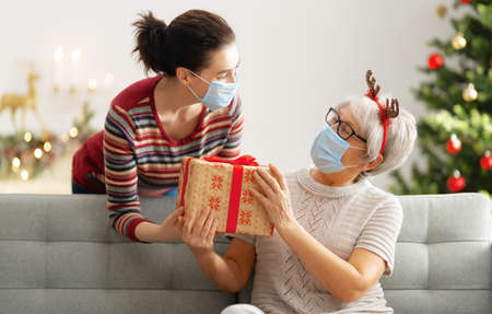 Photo for People with gifts wearing facemasks during coronavirus and flu outbreak on Christmas. Virus and illness protection, home quarantine. COVID-2019 - Royalty Free Image