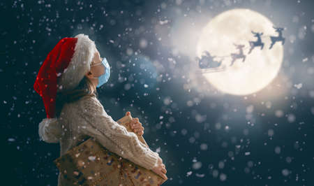 Photo for Merry Christmas! Cute little child with xmas present. Santa Claus flying in his sleigh against moon sky. Happy kid enjoy the holiday. Portrait of girl in face mask with gifts on dark background. - Royalty Free Image