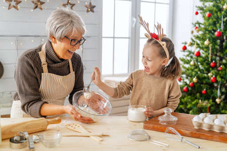 Photo pour Merry Christmas and Happy Holidays. Family preparation holiday food. Grandma and granddaughter cooking cookies. - image libre de droit
