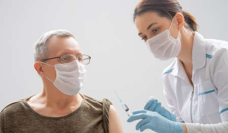 Photo for Doctor giving a senior man vaccination. Virus protection. - Royalty Free Image