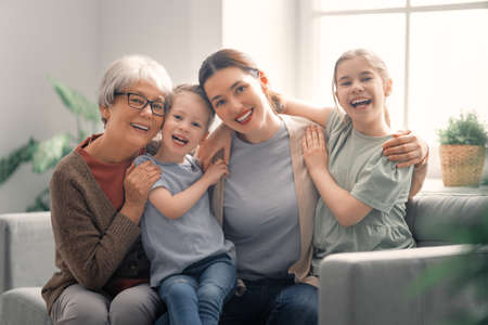 Photo for A nice girls, their mother and grandmother are hugging and  enjoying spending time together at home. - Royalty Free Image