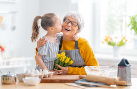 Photo pour Happy loving family are preparing bakery together. Little girl is giving flowers to her granny in the kitchen. - image libre de droit
