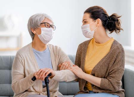 Foto de Adult daughter and senior parent wearing facemasks during flu outbreak. Help for the convalescent. - Imagen libre de derechos
