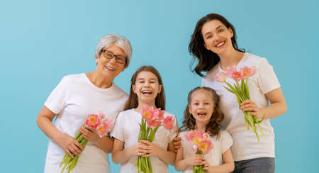 Photo pour Happy women's day! Children daughters are congratulating mom and grandma giving them flowers tulips.Granny, mum and girls smiling on blue wall background. Family holiday and togetherness. - image libre de droit
