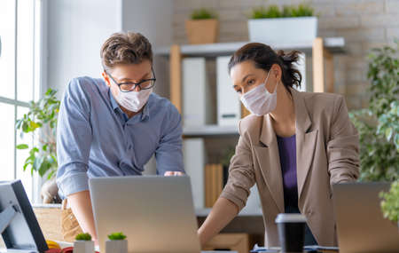 Photo pour Businessman and businesswoman with medical mask working in office. Covid-19 time. - image libre de droit