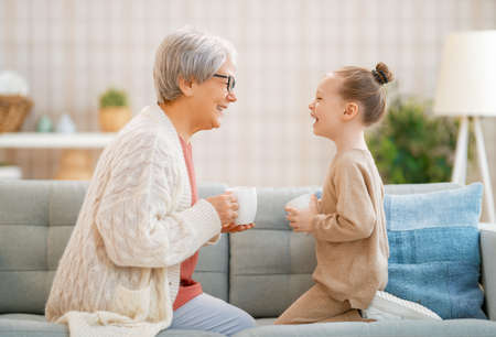 Photo for A nice girl and her grandmother enjoying sunny morning. Good time at home. - Royalty Free Image