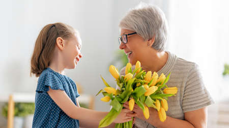 Photo pour Happy mother's day. Child is congratulating granny giving her flowers. Grandma and girl smiling and hugging. Family holiday and togetherness. - image libre de droit