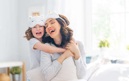 Photo pour A nice girl and her mother enjoying sunny morning. Good time at home. Child wakes up from sleep. Family playing on the bed in the bedroom. - image libre de droit