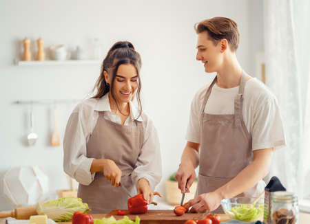 Photo pour Healthy food at home. Happy loving couple is preparing the proper meal in the kitchen. - image libre de droit