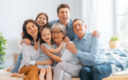 Photo pour Nice girls, their mother, father, grandfather and grandmother are enjoying spending time together at home. Family time. - image libre de droit