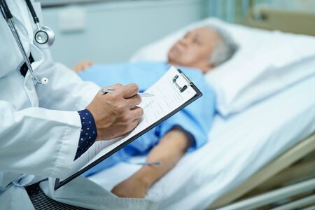 Photo pour Doctor writing down the diagnosis on clipboard while Asian senior or elderly old lady woman  lying on bed in nursing hospital ward : healthy strong medical concept. - image libre de droit