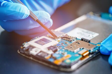 Foto de Asian Technician repairing micro circuit main board of smartphone electronic technology : computer, hardware, mobile phone, upgrade, cleaning concept. - Imagen libre de derechos