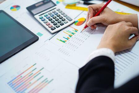 Foto de Accountant working project accounting with graph in modern office. - Imagen libre de derechos